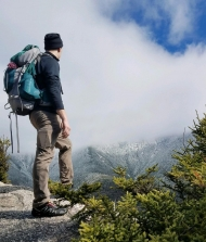Alex Stephanson hiking and looking over the mountain ledge with a blue backpacking backpack