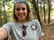 Ellie takes a selfie in the woods, she has a blue and pink head band in her curly hair and her gray americorps t-shirt on